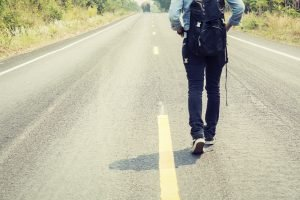 Rear view of a young woman hitchhiking carrying backpack walking on the road